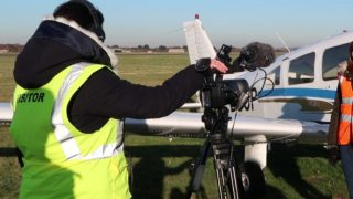 Pure Brand Media filming an interview in front of an airplane on an airfield